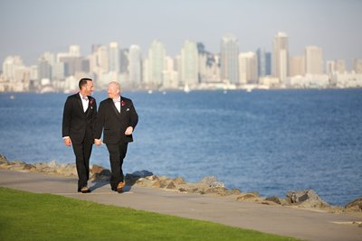 Groom and Groom walking with San Diego Skyline behind them at Tom Ham's Lighthouse