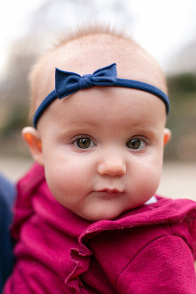 6 month old baby girl with burgundy onesie and navy bow