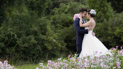 wedding couple standing in flowers
