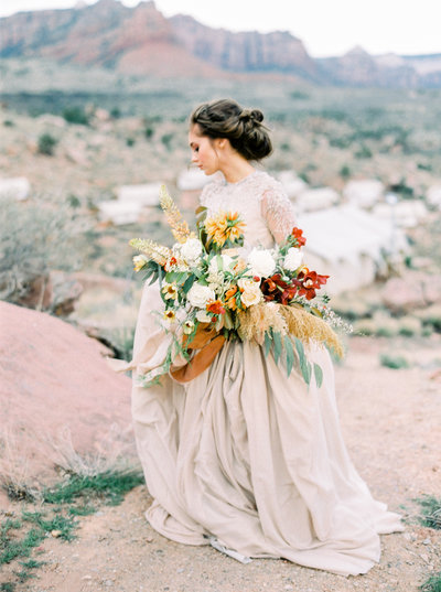 Bride wearing beautiful beige long sleeved wedding gown at Under Canvas Zion National Park  in Utah