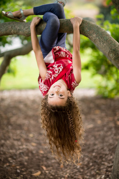 young girl upside down on tree in Arnold Arboretum