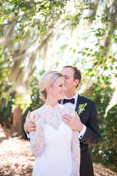 bride and groom kissing under spanish moss