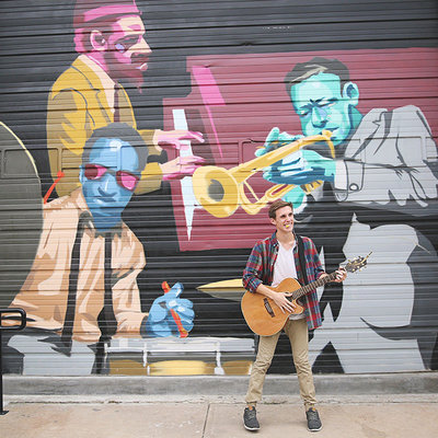 Senior boy singing and playing guitar in downtown Denver, CO by Leighellen Landskov Photography