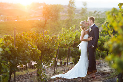 Bride and Groom kissing in vines at Falkner Winery
