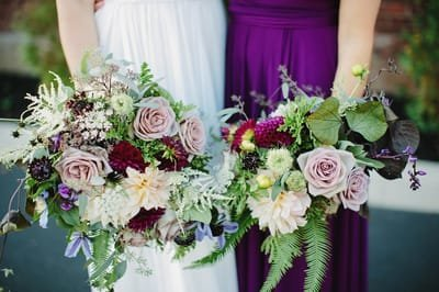 Bride and bridesmaid holding purple bouquets at the Roundhouse in  Beacon, New York. Hudson Valley Wedding florist.