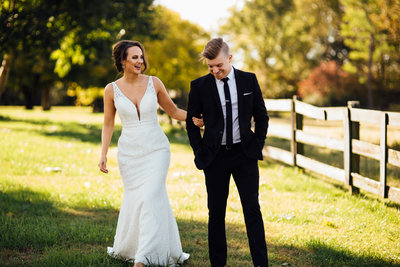 Husband and wife walking and laughter together in Nashville field at Barn in the Bend