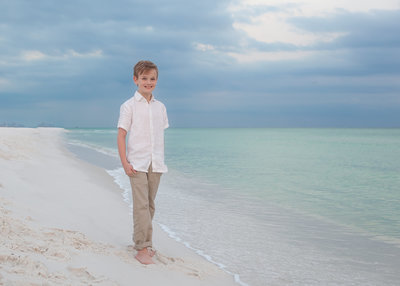 child on the beach smiling for a portrait in the sand on the beach