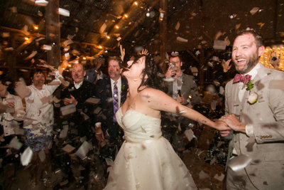 Couple smiling while confetti  falls on them at their wedding