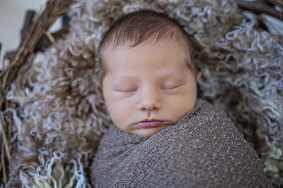 newborn swaddled in brown wrap