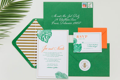 Colorful green and orange monstera wedding invitations with custom calligraphy