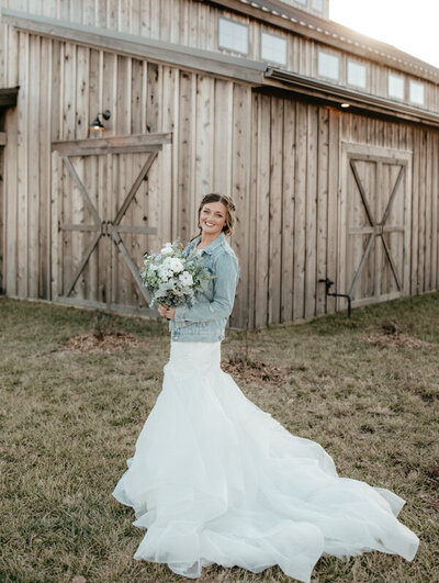 bride smiling and standing holding bouquet