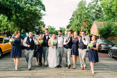 Steph and Jasper walk with their wedding party on the cobble stone street of Historic St. Charles Main Street