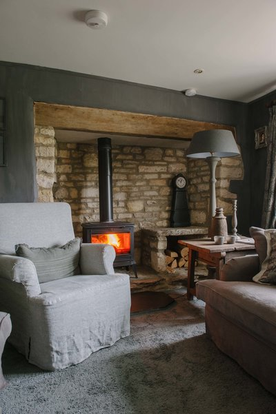Inglenook fireplace with lit fire in the snug at Bank Cottage in the Cotswolds, England. Interior design project by Arte di Vita Interiors.
