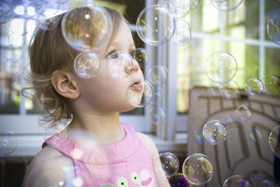 young child stares at a flurry of bubbles all around