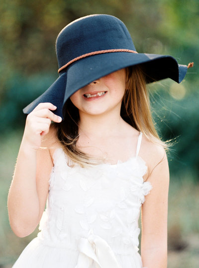 Young girl in white dress with hat over her eyes