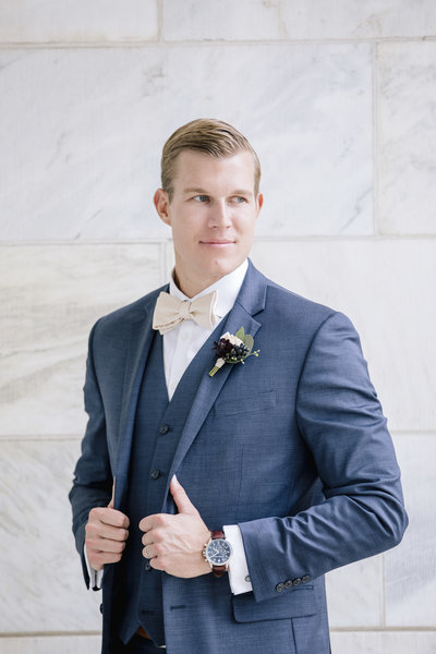 groom in blue tuxedo stands in front of stone wall