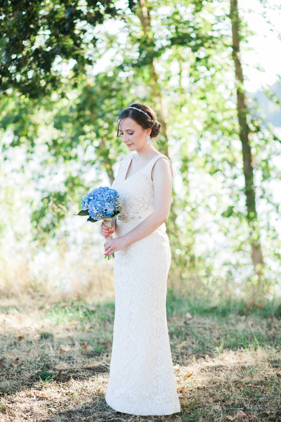 Beautiful photo of Oregon bride holding blue hydrangea bouquet in outdoor field | Susie Moreno Photography