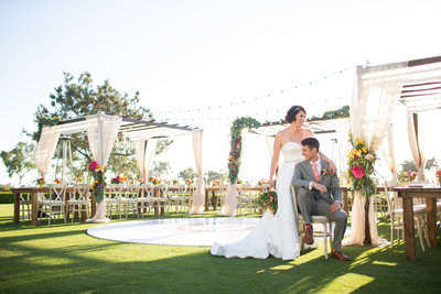 Bride and Groom sitting in their outdoor reception space at The Lodge at Torrey Pines