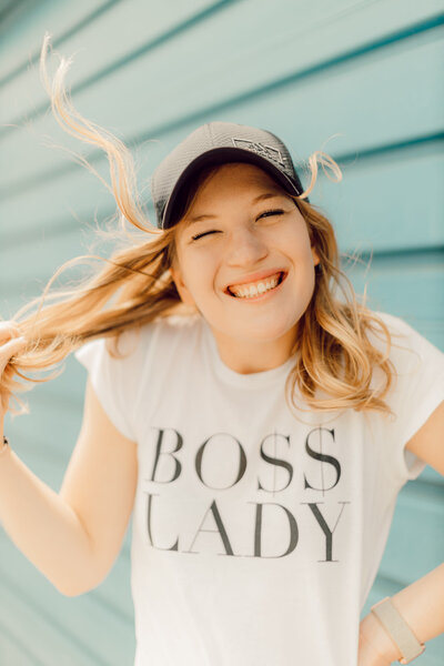 "Joelle smiling with windblown hair in front of a blue wall. She is wearing a white shirt that says ""Boss Lady"" in black text."
