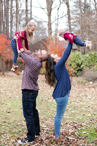 Parents hold daughters above their heads and laugh in fall folliage