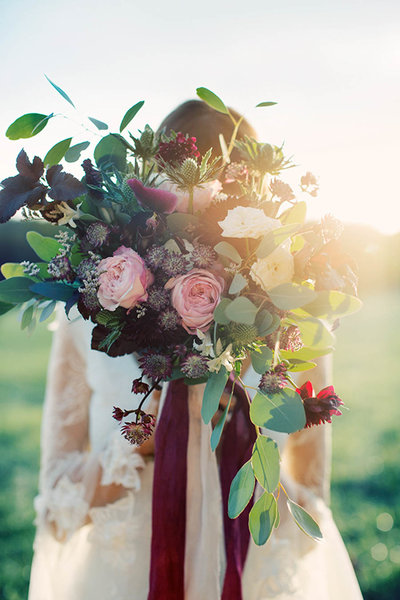 Bride holding a bohemian bridal bouquet in front of her face