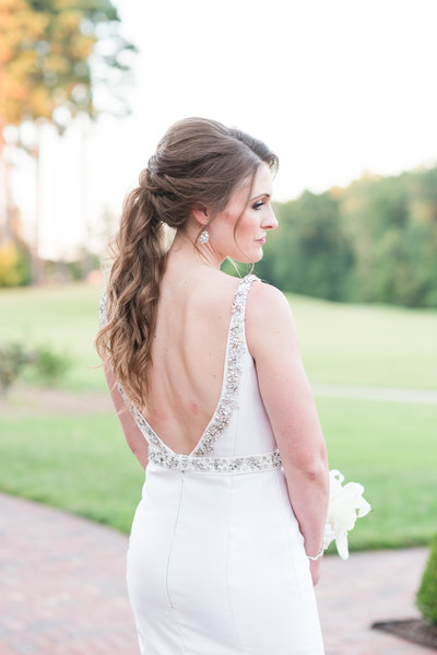 a photograph a bride with a romantic and wavy ponytail updo with the focus on her chic wedding dress at the Grandover Resort