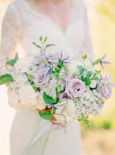 Bride with lace dress and wedding bouquet with dusty purple and white summer flowers