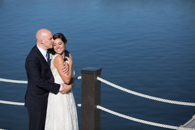 Bride and Groom hugging with Lake behind them at Lakehouse San Marcos