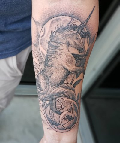 A black and gray tattoo with a flower, animal skull, and stones.