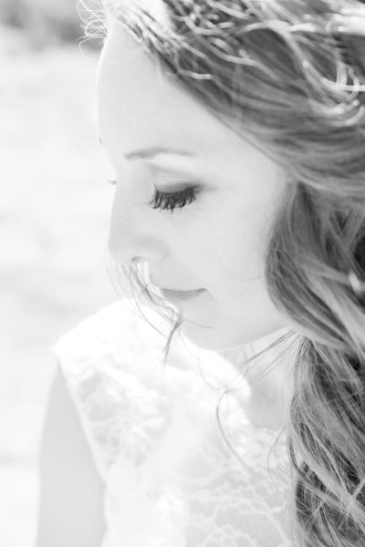 Black and White Photo of bride looking down shoulder, side ponytail, lace wedding dress, dramatic bridal makeup