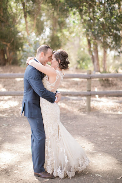 Newly married bride and groom embrace at the Monarch preserve in Pismo beach, California