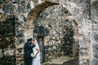 Bride and groom kissing after their wedding at Mission San Jose in San Antonio taken by wedding photographer Expose The Heart
