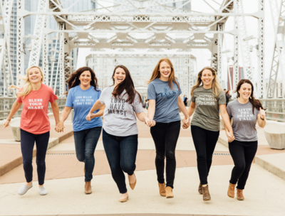 Group of ladies running and laughing together on Nashville pedestrian bridge