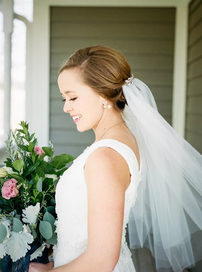 Photo  of an unveiled Bride in her wedding dress holding a bouquet