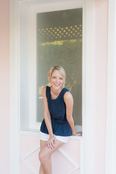 Cassady K Photography laughing  in a window of a pink building
