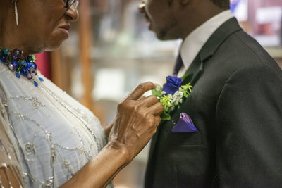 Mother pinning flowers to groomsman veest