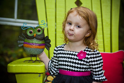 Little girl half pouts half smiles with a cute owl in a bright green chair
