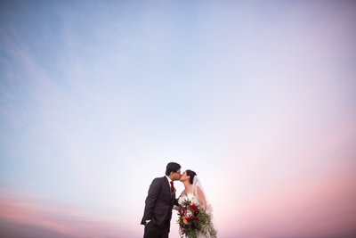 Bride and Groom kissing with pink sky and big bouquet at Coronado Community Center