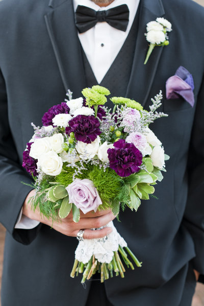 a groom wearing a black suit with a black bowtie holding a white and purple and green wedding bouquet at the Rickhouse in Durham NC