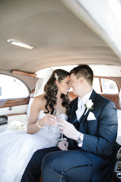 bride and groom in limousine cheers with champagne