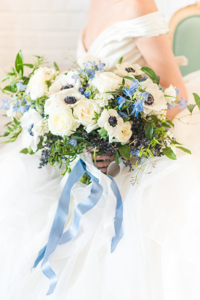 Elegant bride holding a blue and white bouquet with greenery