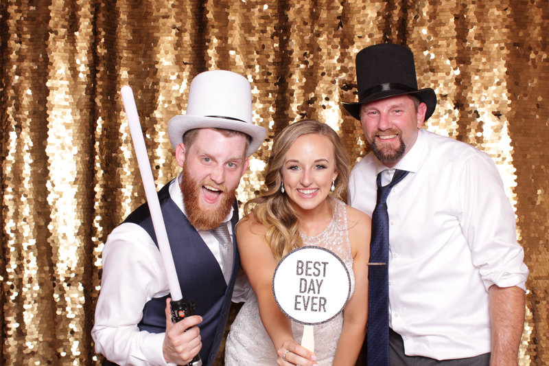 Bride and groom pose with friends at their wedding in the photo booth