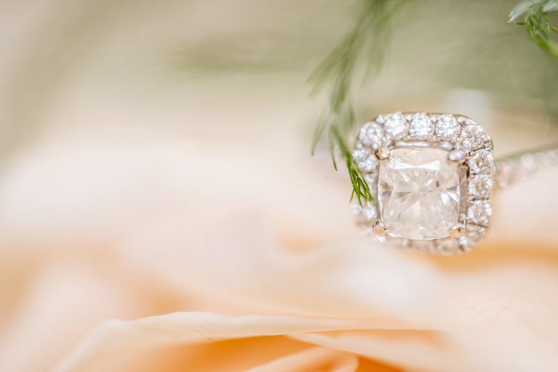 diamond ring sits on peach flowers