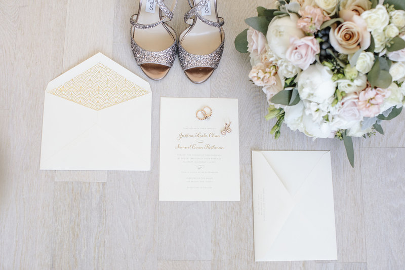 wedding invitations rings and flowers on grey wood floor