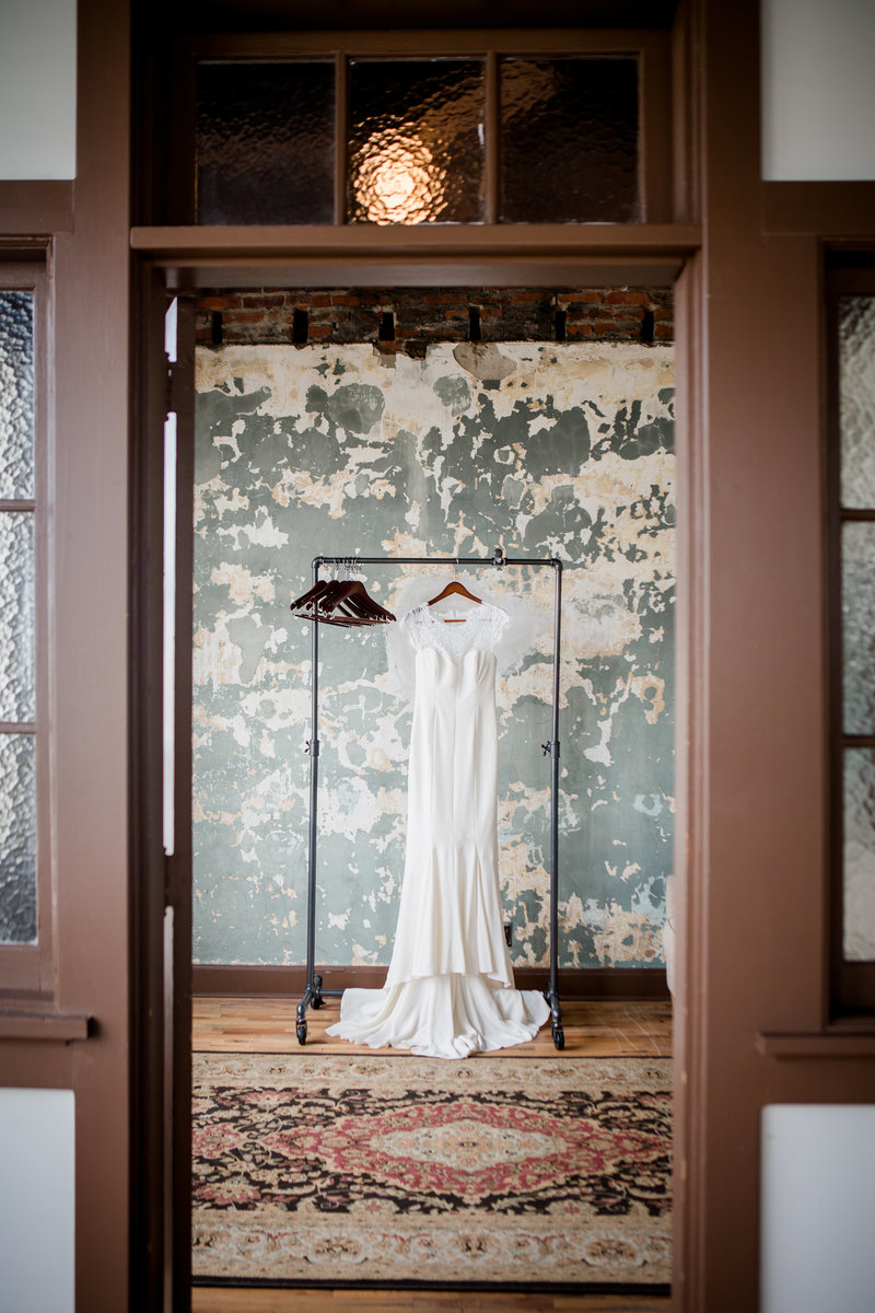 Bride's dress hanging on pipe clothing line at The Standard Wedding Venue by Knoxville Wedding Photographer, Amanda May Photos.