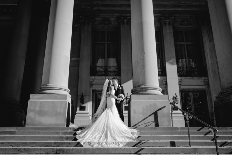 black and white bride and groom on grand steps at monmouth university