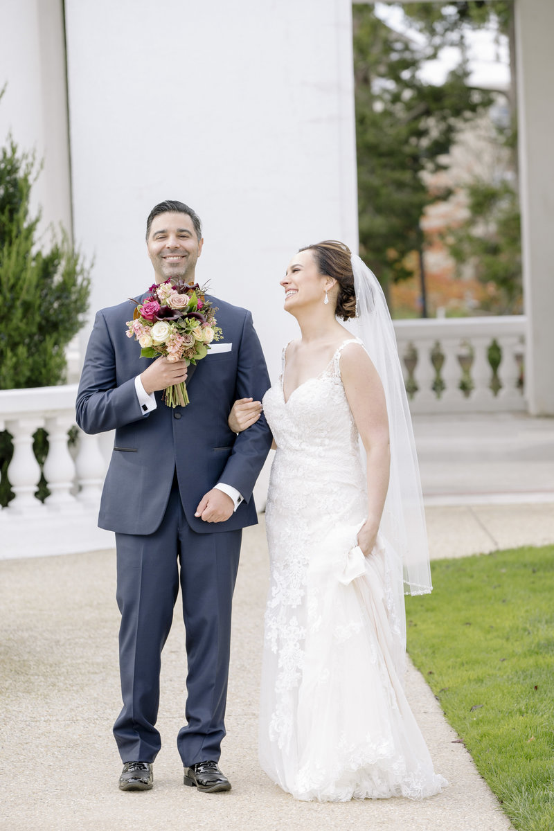 candid moment of groom holds flowers and brides laughs