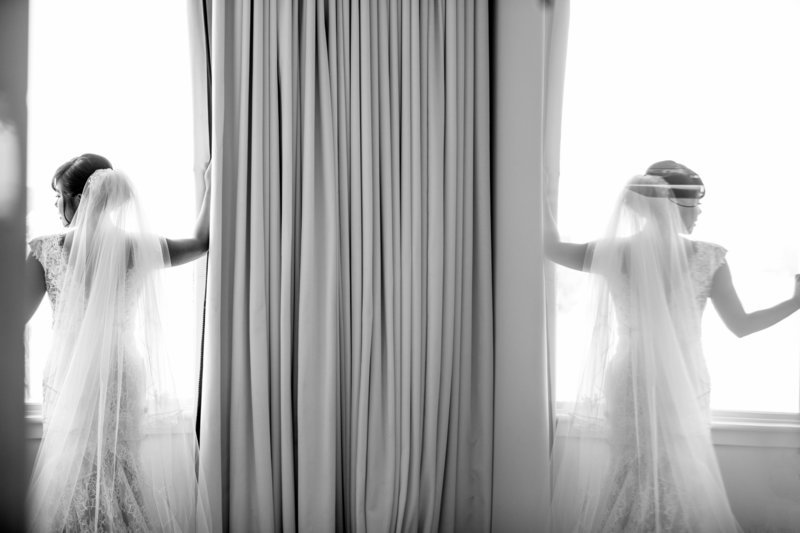 black and white bride looking out window with reflection