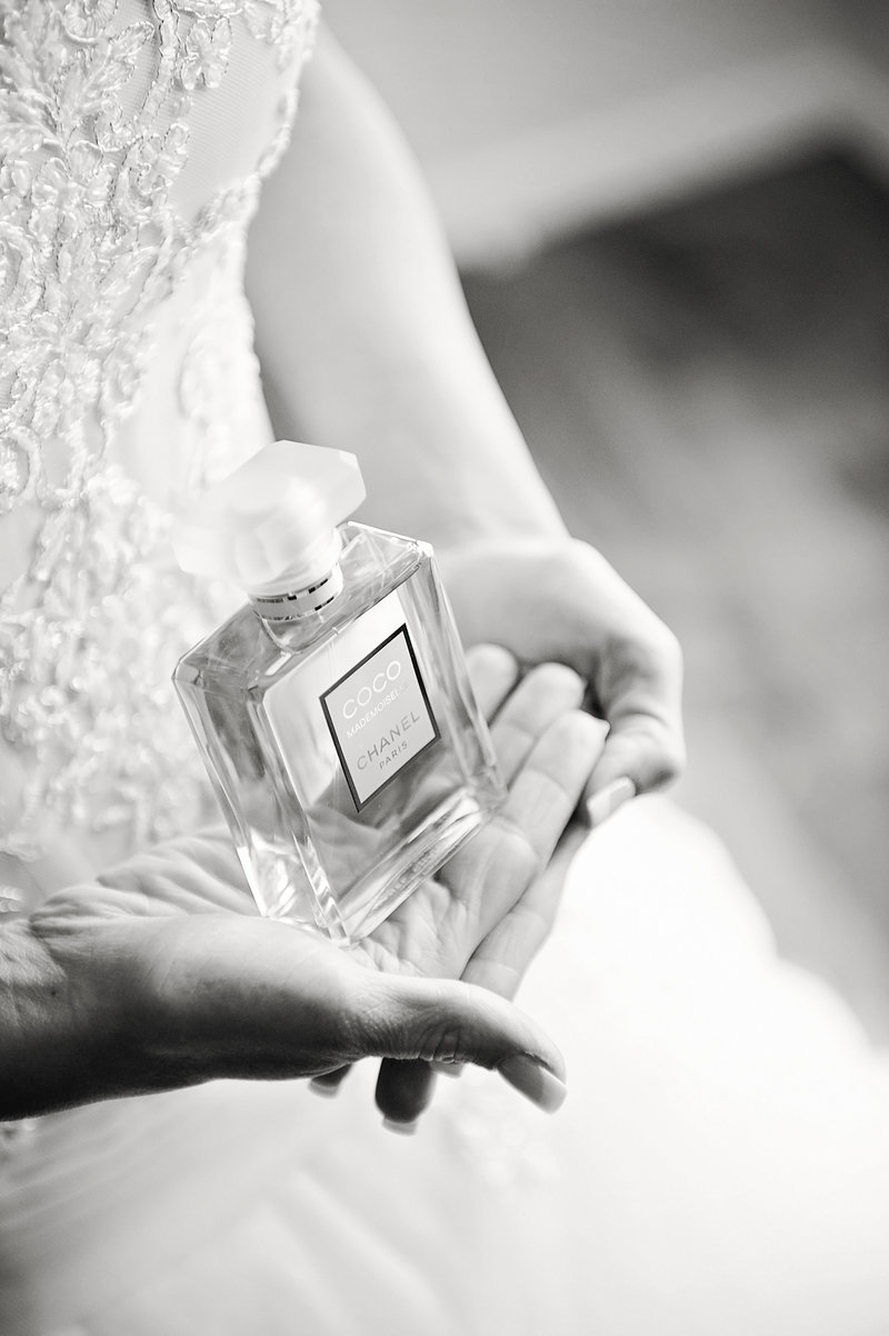 black and white bride holds perfume bottle in hands chanel