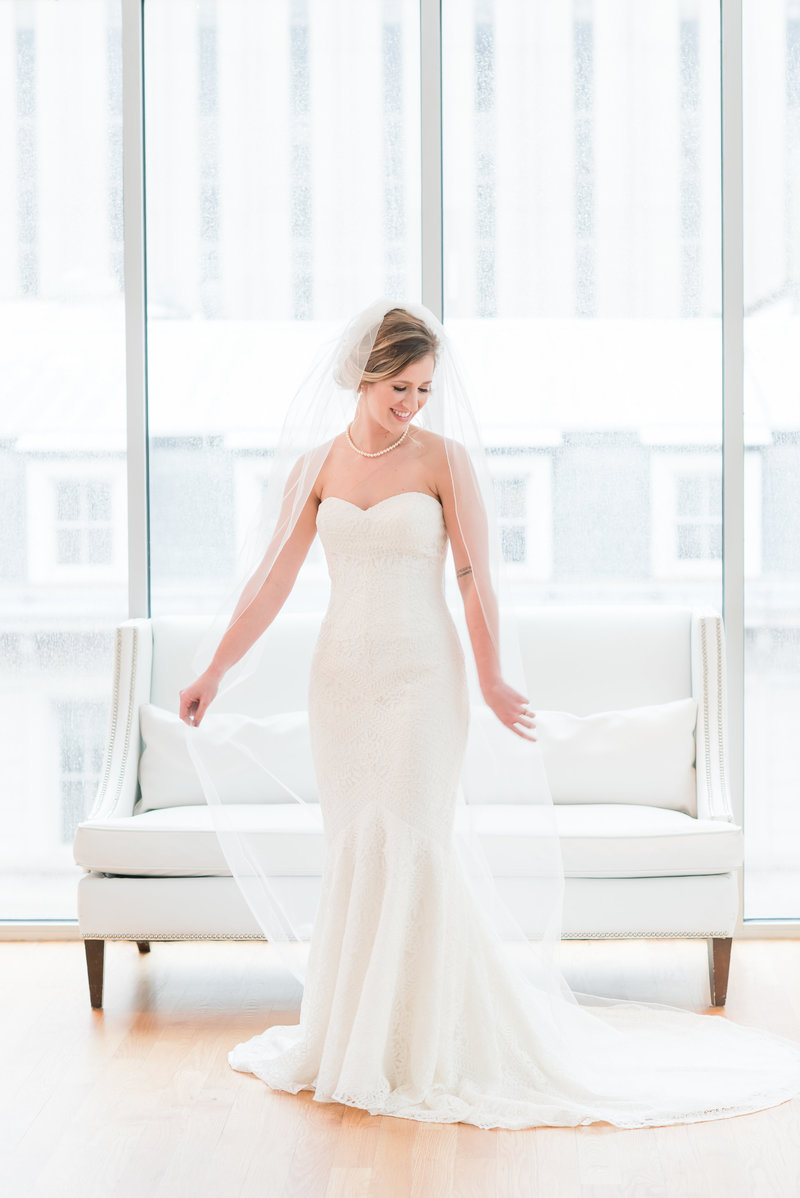 A bride holding a cathedral length veil in front of white couch in Raleigh